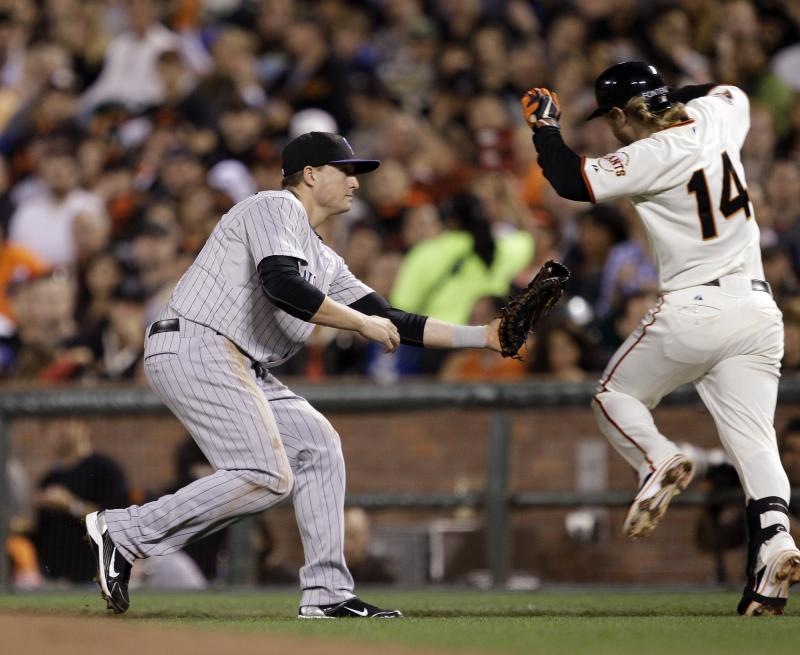 Colorado Rockies first baseman Jordan Pacheco, left, tags out San Francisco Giants' Mike Fontenot after being drawn off base by a wide throw during the third inning of a baseball game in San Francisco,  Tuesday, Sept. 27, 2011. (AP Photo/Marcio Jose Sanchez)
