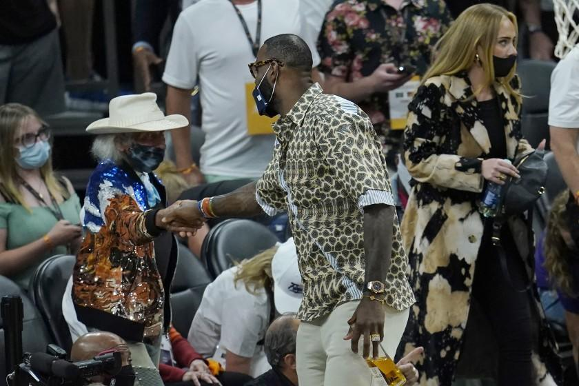 Los Angeles Lakers basketball player LeBron James, middle, greets fan James Goldstein during Game 5 of basketball's NBA Finals between the Phoenix Suns and the Milwaukee Bucks, Saturday, July 17, 2021, in Phoenix. Also pictured is musician Adele, right. (AP Photo/Ross D. Franklin)