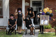 The family of Larry Hammond wave as a line of cars with friends and family, who could not attend his funeral due to the coronavirus, pass by their home, in New Orleans, Wednesday, April 22, 2020. Hammond was Mardi Gras royalty, and would have had more than a thousand people marching behind his casket in second-line parades. (AP Photo/Gerald Herbert)
