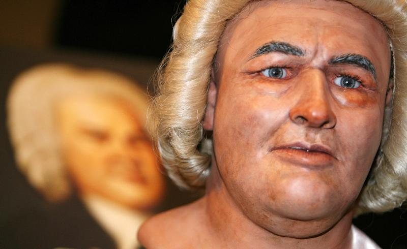 A reconstruction of the face of Johann Sebastian Bach (1685-1750) next to a painting of the German composer