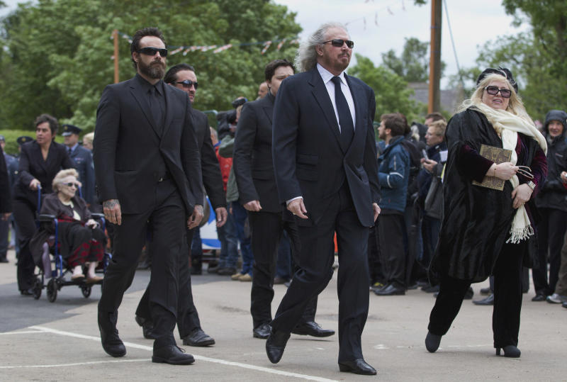 Barry Gibb, second, left with Dwina Gibb walks behind Robin Gibb's funeral procession as they walk from the family home to St Mary's Church in Thame, England, Friday, June 8, 2012. Robin Gibb a member of the iconic Bee Gees pop group died May 20, after a long battle with cancer.(AP Photo/Alastair Grant)