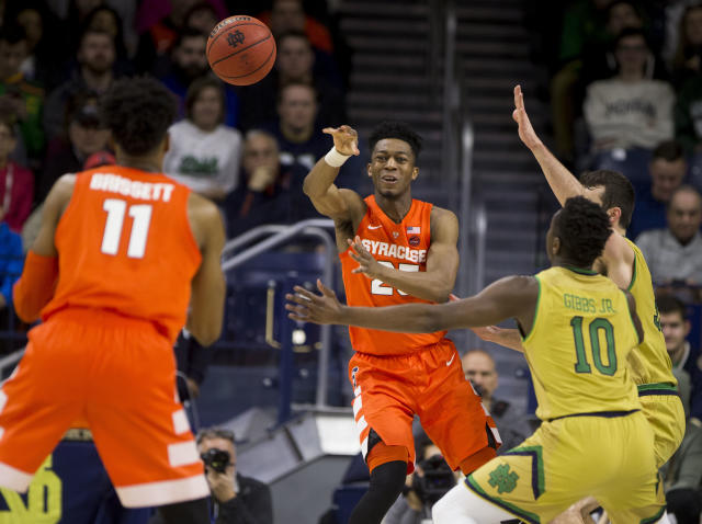 Syracuse's Tyus Battle (25) passes to teammate Oshae Brissett (11), next to Notre Dame's T.J. Gibbs Jr. (10) and John Mooney during the second half of an NCAA college basketball game Saturday, Jan. 5, 2019, in South Bend, Ind. Syracuse won 72-62. (AP Photo/Robert Franklin)