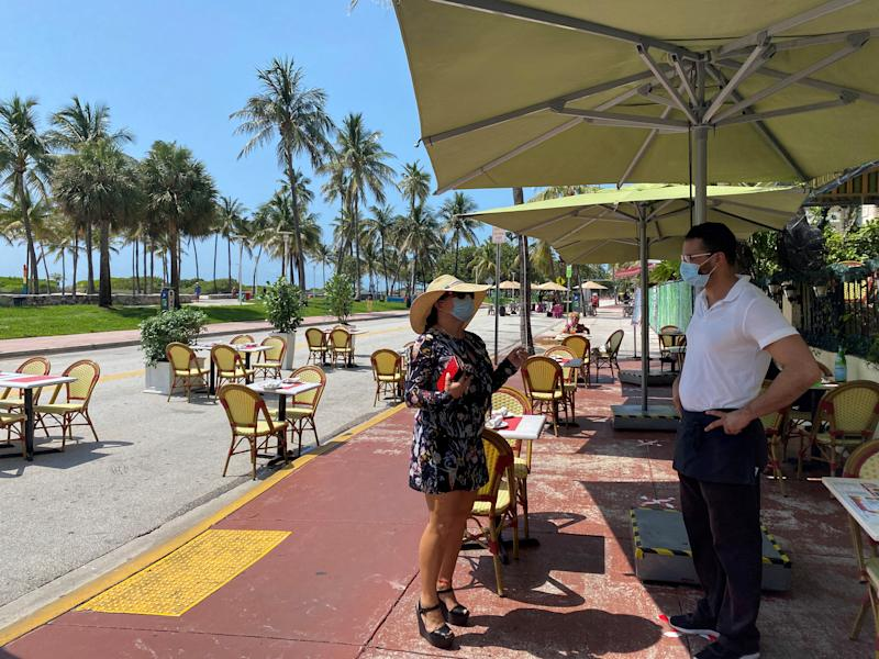A general manager of Il Giardino wearing a mask while standing on Ocean Drive on South Beach, in Miami, Florida.