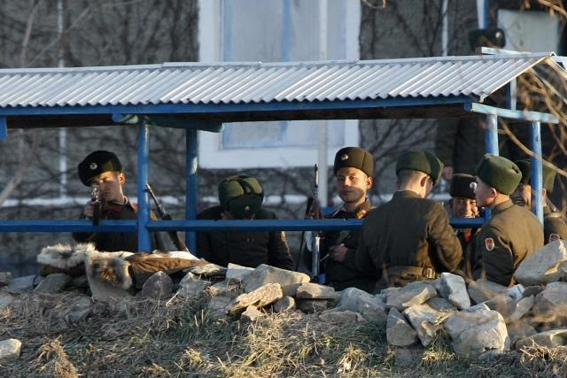 A North Korean soldier aims his rifle at tourist boat as he and other soldiers stand guard on the banks of Yalu River