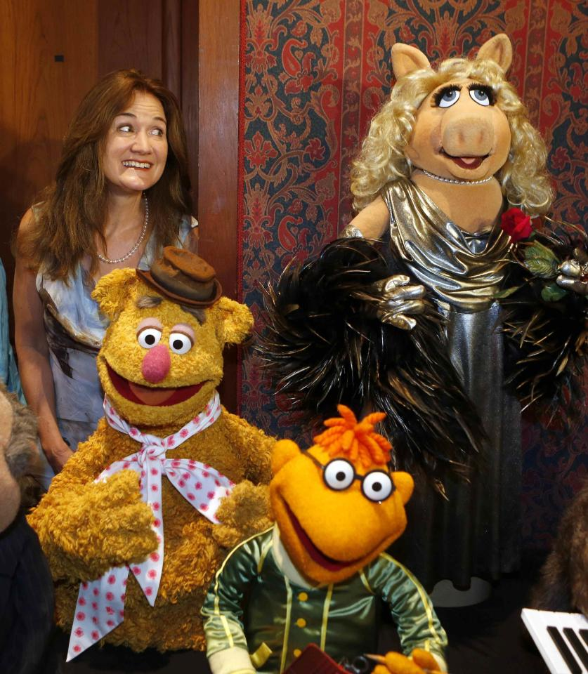 Cheryl Henson, daughter of Muppets founder Jim Henson, poses after donating Miss Piggy (R) and other puppets famous from the Sesame Street and Muppets television series to the Smithsonian's National Museum of American History in Washington September 24, 2013. REUTERS/Larry Downing (UNITED STATES - Tags: SOCIETY ENTERTAINMENT)