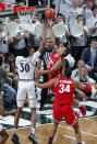 Ohio State's CJ Walker (13) puts up a layup against Michigan State's Marcus Bingham Jr. (30) during the first half of an NCAA college basketball game, Sunday, March 8, 2020, in East Lansing, Mich. (AP Photo/Al Goldis)
