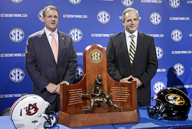 Auburn head coach Gus Malzahn, left, poses for a photo with Missouri head coach Gary Pinkel at a press conference ahead of Saturday's Southeastern Conference championship college football game, Friday, Dec. 6, 2013, in Atlanta. (AP Photo/David Goldman)