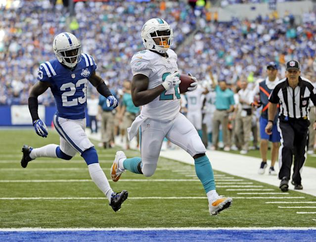 Miami Dolphins' Lamar Miller (26) runs in for a 10-yard for touchdown past Indianapolis Colts' Vontae Davis (23) during the first half an NFL football game Sunday, Sept. 15, 2013, in Indianapolis. (AP Photo/Michael Conroy)