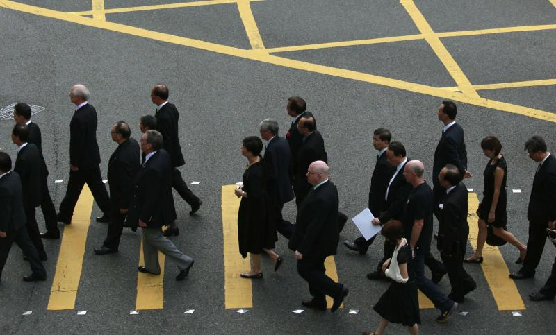Hong Kong lawyers cross a street as they stage a silent march from the High Court to the Court of Final Appeal in Hong Kong