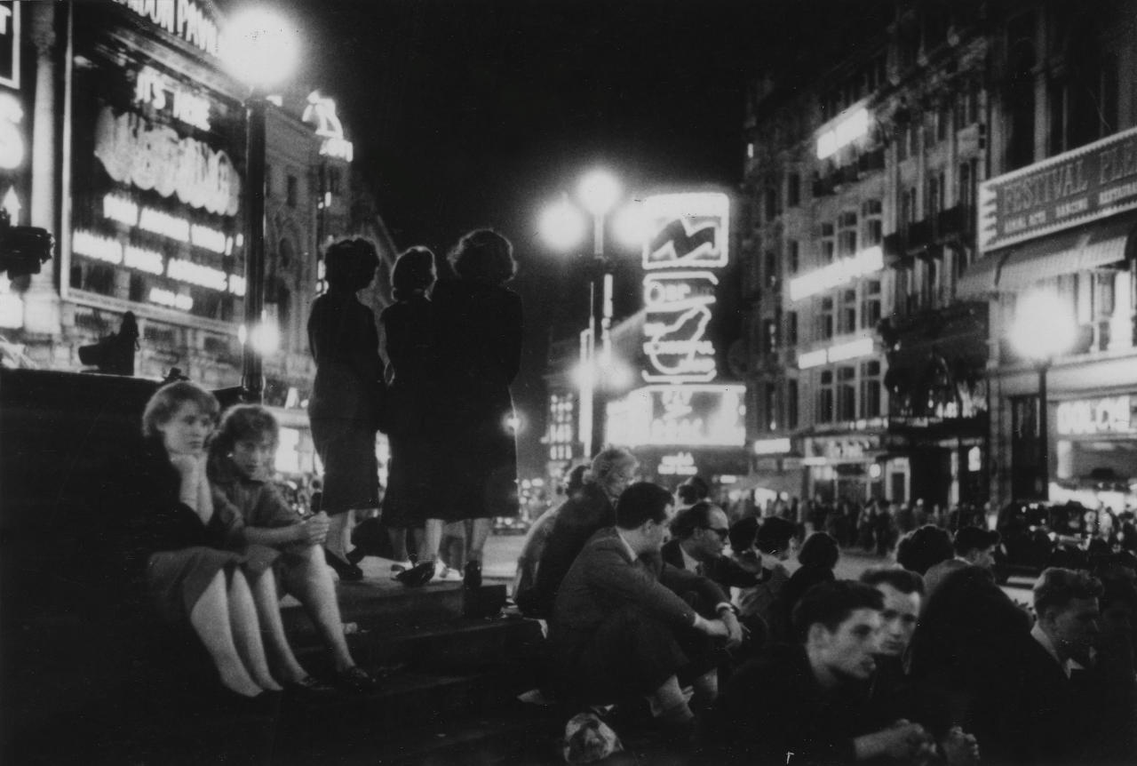 Men and women sit on the steps of a fountain at Picadilly Circus, London in 'Picadilly Circus', 1953. Bert Hardy was born into a working class family in Blackfriars, London (Bert Hardy/Getty Images)