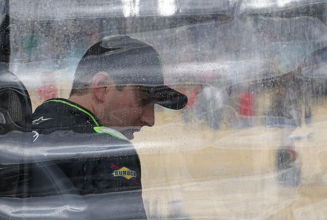 Kyle Busch waits out a rain delay at his team stall on pit road during a NASCAR Nationwide auto race Saturday, March 1, 2014, in Avondale, Ariz. (AP Photo/Ross D. Franklin)