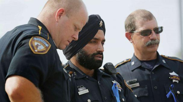 PHOTO: In this Aug. 30, 2015, photo, Harris County Sheriff's Deputy Sandeep Dhaliwal, center, grieves with Deputies Dixon, left, and Seibert, right, at a memorial for Deputy Darren Goforth, at the Chevron where he was killed, in Houston. (Jon Shapley/Houston Chronicle via AP)