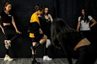 Instructor Pham Kieu Ly (2nd L) demonstrates a pose to participants