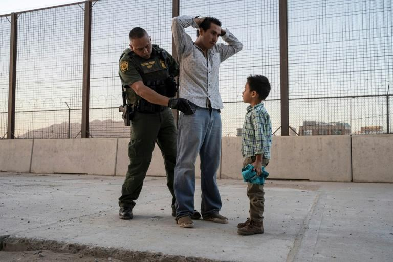 A US border guard searches a migrant in front of his son in El Paso, Texas