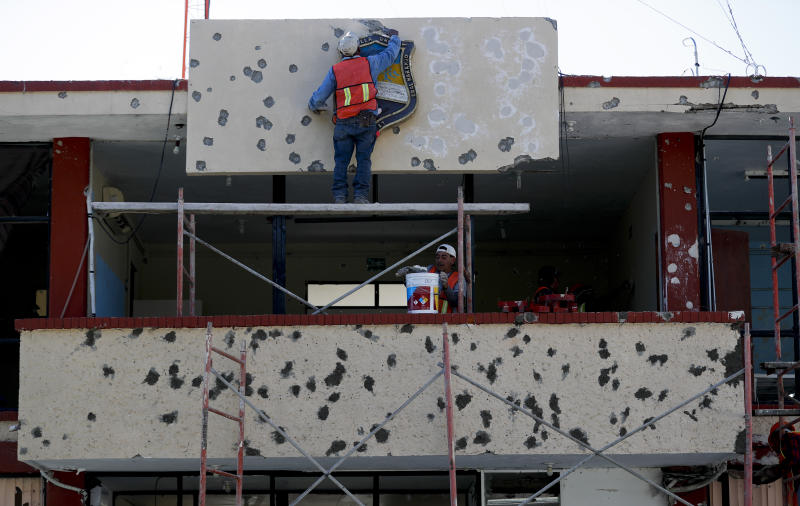 Workers repair the facade of City Hall riddled with bullet holes, in Villa Union, Mexico, Monday, Dec. 2, 2019. The small town near the U.S.-Mexico border began cleaning up Monday even as fear persisted after 22 people were killed in a weekend gun battle between a heavily armed drug cartel assault group and security forces. (AP Photo/Eduardo Verdugo)