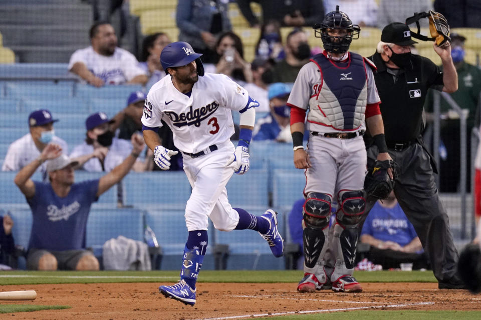 Los Angeles Dodgers' Chris Taylor, left, runs to first as he hits a three-run home run as Washington Nationals catcher Yan Gomes watches during the second inning of a baseball game Saturday, April 10, 2021, in Los Angeles. (AP Photo/Mark J. Terrill)