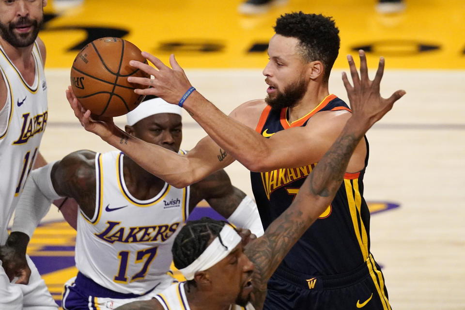 Golden State Warriors guard Stephen Curry, right, passes the ball while under pressure from Los Angeles Lakers guard Dennis Schroder, left, and guard Kentavious Caldwell-Pope, below, during the first half of an NBA basketball game Sunday, Feb. 28, 2021, in Los Angeles. (AP Photo/Mark J. Terrill)