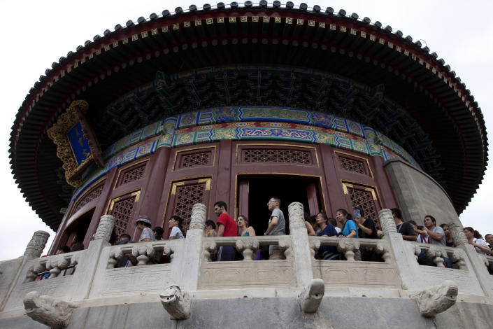 In this Aug. 7, 2013 photo, two foreign tourists, center, line up with Chinese tourists as they tour the Temple of Heaven in Beijing. China, one of the most visited countries in the world, has seen sharply fewer tourists this year, with worsening air pollution partly to blame. (AP Photo/Alexander F. Yuan)