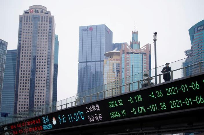 FILE PHOTO: A man stands on an overpass with an electronic board showing Shanghai and Shenzhen stock indexes in Shanghai