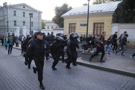 Law enforcement officers run along a street after a rally to demand authorities allow opposition candidates to run in a local election in Moscow