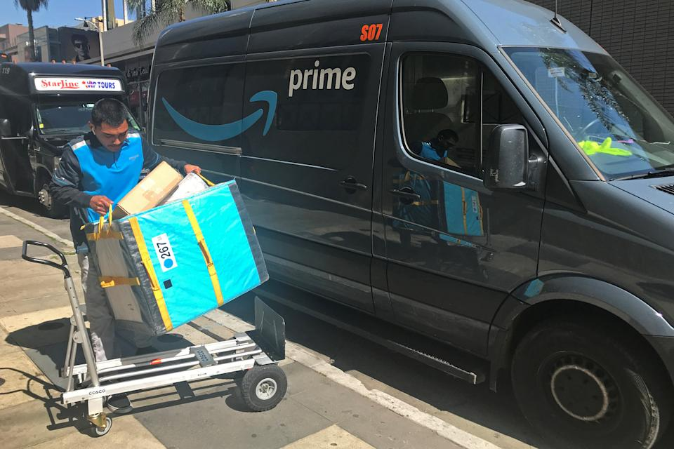 An Amazon worker loads a trolley from a Prime delivery van.