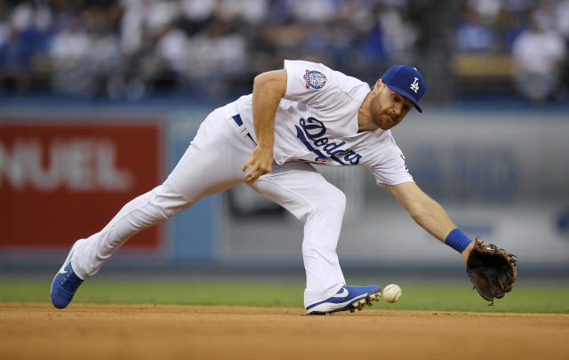 Los Angeles Dodgers second baseman Logan Forsythe fields a ball hit by San Francisco Giants' Brandon Crawford during the sixth inning of a baseball game Saturday, June 16, 2018, in Los Angeles. Crawford was thrown out at first on the play. (AP Photo/Mark J. Terrill)