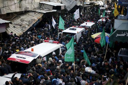 Mourners gather around ambulances carrying the bodies of seven Palestinian Hamas gunmen, who were killed when a tunnel collapsed close to the Gaza Strip's eastern border with Israel during their funeral in Gaza City, January 29, 2016. REUTERS/Suhaib Salem