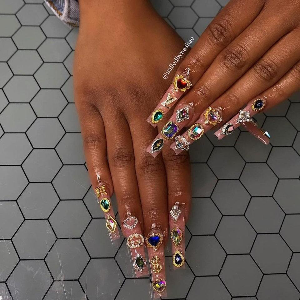 """Mississippi-based nail artist <a href=""""https://www.instagram.com/nailedbynashae/"""" rel=""""nofollow noopener"""" target=""""_blank"""" data-ylk=""""slk:Axayla Nashae"""" class=""""link rapid-noclick-resp"""">Axayla Nashae</a> created this bejeweled acrylic set that looks like it's fit for royalty. To create the set, she tells <em>Allure</em> she started off with a nude acrylic powder mixed with a shimmer powder for a subtle glitter effect. Then, she added the multicolored gems, including the Gucci logo, on each nail, drawing inspiration from images of Black women's nails from the '90s to figure out the placement."""