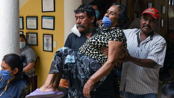 Relatives carry a woman with symptoms of Covid-19 in Chiapas state