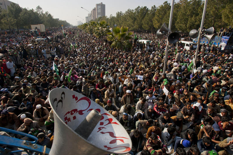 Supporters of Pakistani Sunni Muslim cleric Tahir-ul-Qadri listen to a speech by ul-Qadri, unshown, at an anti-government rally in Islamabad, Pakistan on Tuesday, Jan. 15, 2013. Thousands of anti-government protesters are rallying in the streets of Pakistani capital for second day despite early-morning clashes with police who fired shots and tear gas to disperse the crowd. (AP Photo/Anjum Naveed)