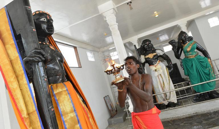 A Hindu priest lights a coconut oil lamp in front of a statue of god Skanda, a deity believed to be a protector of the island, at the Sri Subramaniam temple in Matara on March 7, 2014
