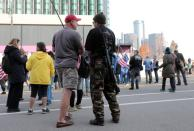 A man carries a weapon as supporters of U.S. President Donald Trump protest the election outside the TCF Center in Detroit