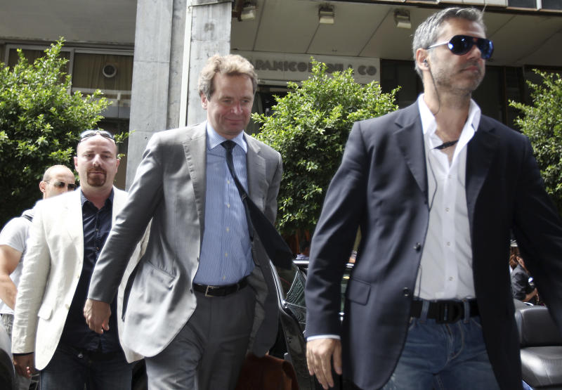 International Monetary Fund (IMF) mission chief Poul Thomsen, centre, arrives with plainclothes police for another meeting between Greece's new Finance Minister Yannis Stournaras and the debt inspectors from the European Central Bank, European Commission and International Monetary Fund,  known as the troika at Greece's Finance Ministry in Athens, Thursday, Aug. 2, 2012. Greek Prime Minister Antonis Samaras on Wednesday talked coalition government partners into accepting the new spending cuts demanded by the debt-crippled country's bailout creditors. (AP Photo/Thanassis Stavrakis)