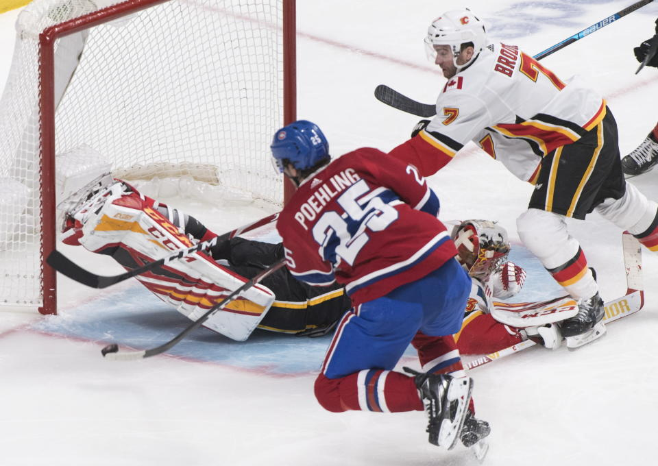 Montreal Canadiens' Ryan Poehling scores against Calgary Flames goaltender David Rittich as Flames' TJ Brodie defends during third period NHL hockey action in Montreal, Monday, Jan. 13, 2020. (Graham Hughes/The Canadian Press via AP)