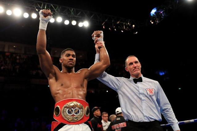 Anthony Joshua raises his arms in celebration after knocking out Eric Molina in his second title defense. (Getty Images)