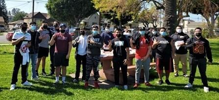 "Roosevelt football players gather at a local park to pick up memorabilia of ""Coach Dicky"" from Guillen's family."