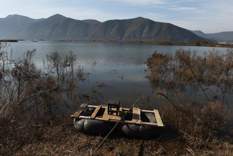A home-made raft sits beside an expanded section of the Danjiangkou reservoir near Jianying village in China's central Henan province, November 3, 2014 (AFP Photo/Greg Baker)