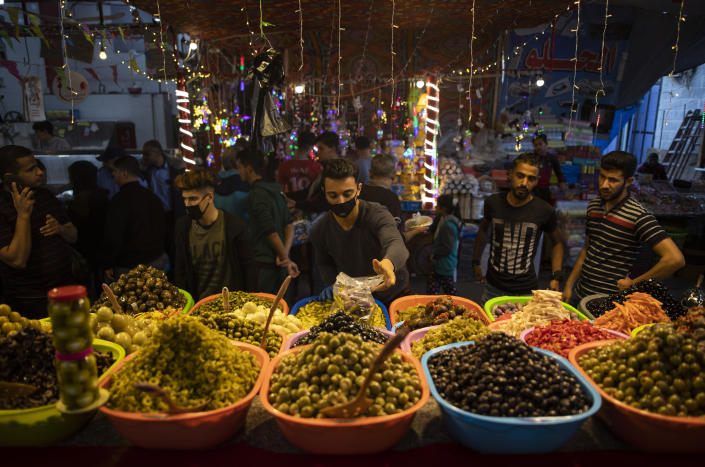 A Palestinian vendor wears a face mask as a protection against the spread of the coronavirus as he sells pickles in the Zawiya market during a Ramadan day in Gaza City, Tuesday, April 28, 2020. (AP Photo/Khalil Hamra)