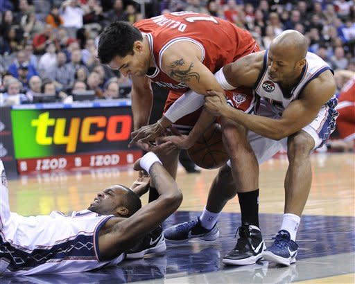 New Jersey Nets' Shelden Williams, left, battles for a loose ball with Milwaukee Bucks' Carlos Delfino, of Argentina, and Nets' Sundiata Gaines, right, during the first quarter of an NBA basketball game Sunday, Feb. 19, 2012, in Newark, N.J. (AP Photo/Bill Kostroun)
