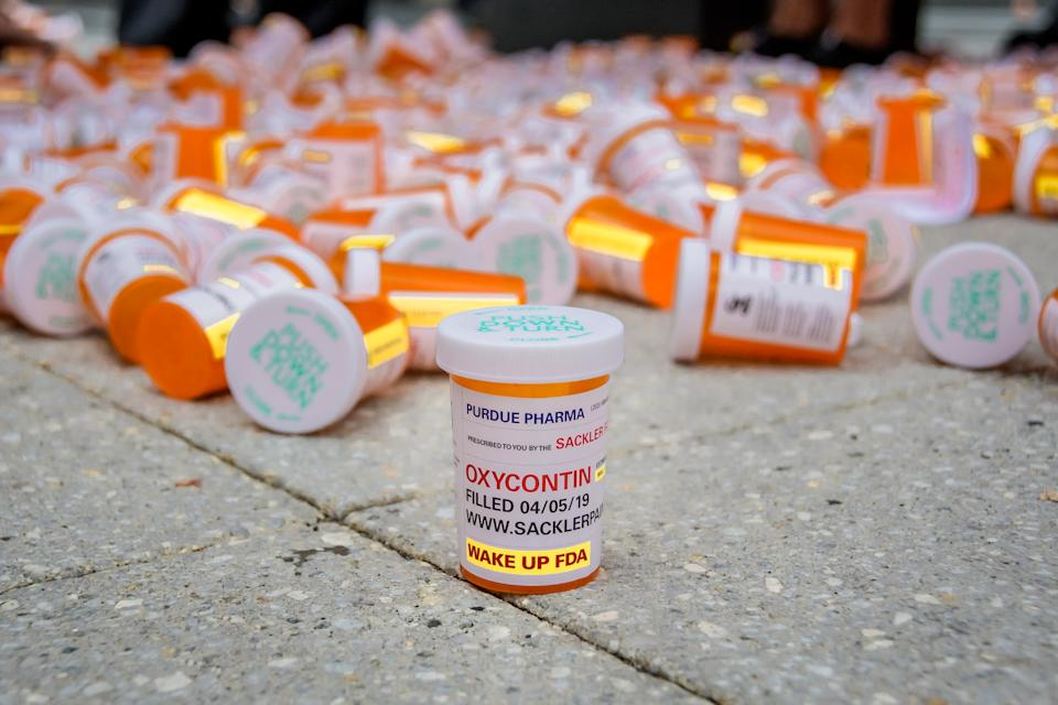 """PURDUE PHARMA, STAMFORD, CT, UNITED STATES - 2019/09/12: Members of P.A.I.N. (Prescription Addiction Intervention Now) and Truth Pharm staged a protest on September 12, 2019 outside Purdue Pharma headquarters in Stamford, over their recent controversial opioid settlement. Participants dropped hundreds prescription bottles of OxyContin while holding tombstones with the names of opioids casualties and banners reading """"Shame on Sackler"""" and """"200 Dead Each Day"""". (Photo by Erik McGregor/LightRocket via Getty Images)"""