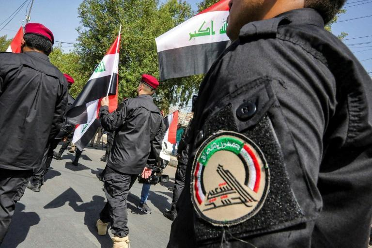 Members of Iraq's Hashed al-Shaabi paramilitary forces march in a symbolic funerary parade in the capital Baghdad on June 29 in remembrance of those killed in a US raid against one of the Hashed's brigades