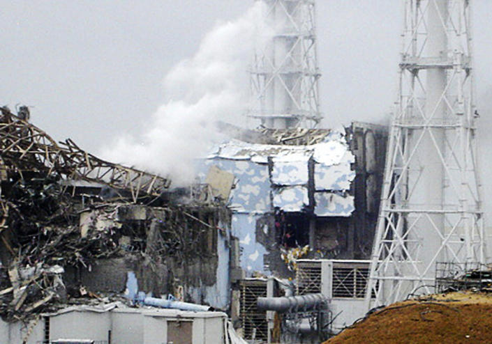 FILE - This file image made available from Tokyo Electric Power Co. via Kyodo News shows the damaged No. 4 unit of the Fukushima Daiichi nuclear complex in Okuma town, northeastern Japan, on Tuesday, March 15, 2011. White smoke billows from the No. 3 unit. A decade ago, the Fukushima Daiichi nuclear power plant melted down. It looked like a bombed-out factory in a war zone. Emergency workers risked their lives as they battled to keep the crisis in check. Eeriness is no longer there. The feeble-looking plastic hoses mended with tape and the outdoor power switchboard that rats got into, causing blackouts, were replaced with proper equipment. (Tokyo Electric Power Co/Kyodo News via AP, File)