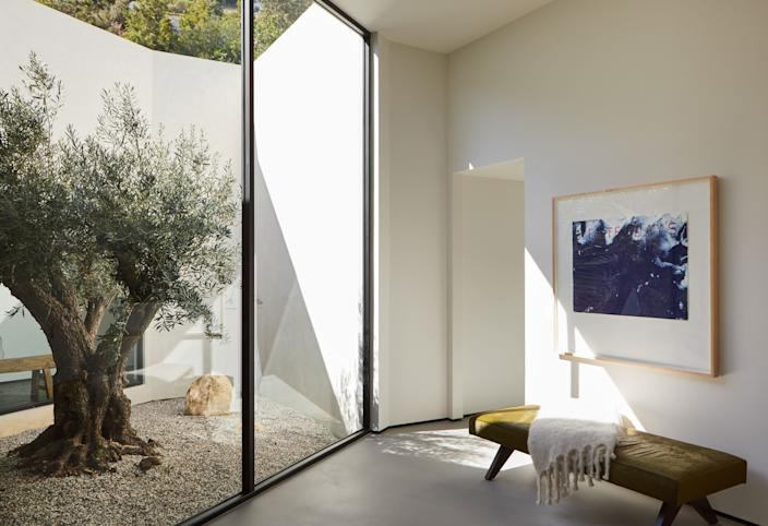 """<div class=""""caption""""> A light-filled room with a view of an olive tree from the late 1800s. The Pierre Jeanneret daybed was reupholstered in Cavallini olive pony hair from <a href=""""https://www.edelmanleather.com/"""" rel=""""nofollow noopener"""" target=""""_blank"""" data-ylk=""""slk:Edelman"""" class=""""link rapid-noclick-resp"""">Edelman</a> and the artwork, <em>Yesterday's Treasures</em> (1989), is by Ed Ruscha. </div>"""