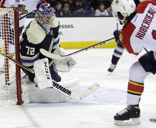Columbus Blue Jackets' Sergei Bobrovsky, left, of Russia, makes a save against Florida Panthers' Jonathan Huberdeau during the third period of an NHL hockey game on Saturday, Feb. 1, 2014, in Columbus, Ohio. The Blue Jackets won 4-1. (AP Photo/Jay LaPrete)