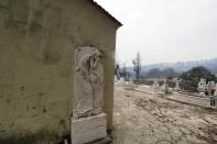 A burnt cemetery during a wildfire in Kirinthos village on the island of Evia, about 135 kilometers (84 miles) north of Athens, Greece, Friday, Aug. 6, 2021. Thousands of people fled wildfires burning out of control in Greece and Turkey on Friday, including a major blaze just north of the Greek capital of Athens that claimed one life, as a protracted heat wave left forests tinder-dry and flames threatened populated areas and electricity installations. (AP Photo/Thodoris Nikolaou)