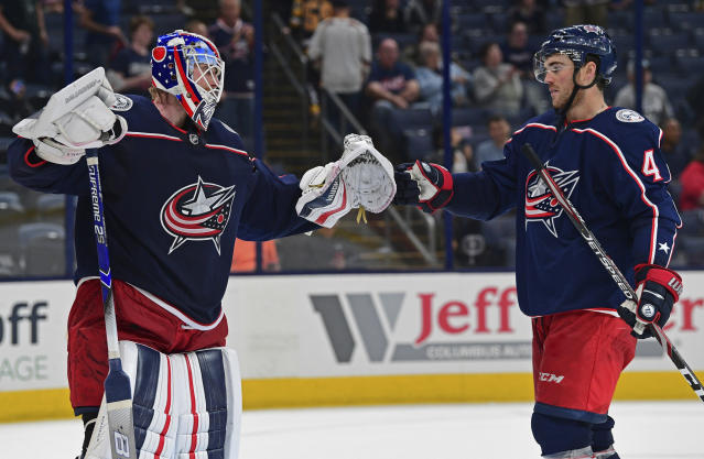 Columbus Blue Jackets goalie Joonas Korpisalo, left, is congratulated by Scott Harrington after the Blue Jackets defeated the Pittsburgh Penguins 3-1 in a preseason NHL hockey game, Saturday, Sept. 21, 2019, in Columbus, Ohio. (AP Photo/David Dermer)