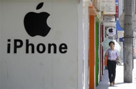 A woman walks past a logo of Apple Inc in Wuhan
