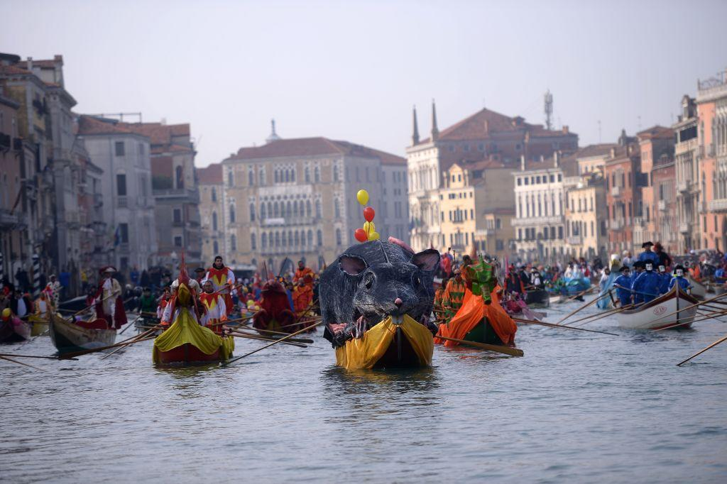 <p>Bright coloured boats filled with costumed revellers move along Venice, Italy's Grand Canal during the opening regatta of the Venice Carnival on January 28, 2018. Photo by Filippo Monteforte/AFP/Getty Images. </p>