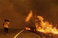 A cameraman films flames flames from the LNU Lightning Complex fires in Vacaville, Calif., on Wednesday, Aug. 19, 2020. Fire crews across the region scrambled to contain dozens of wildfires sparked by lightning strikes. (AP Photo/Noah Berger)