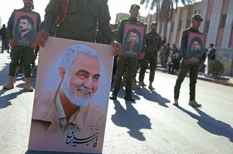A member of the Hashed al-Shaabi, an Iraqi paramilitary network dominated by Iran-backed factions, carries a portrait of Soleimani